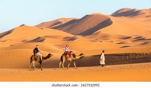 Merzouga / Morocco - March 26th, 2018: Two tourists riding camels by the Erg Chebbi dunes in the Sahara at sunset