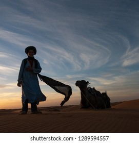 Merzouga, Morocco - October 21, 2018: Guide posing for photoshoot with camels in the background in a desert in the evening during sunset