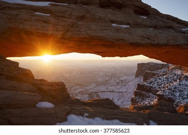 Mesa Arch sunrise in Canyonlands National Park near Moab, Utah, USA.  This rare wintertime scenic with snow and red rocks is a tourist attraction of the southwestern deserts and Colorado Plateau.