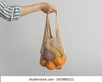 Mesh bag with fruits in female hand. Hand of Stylish young woman hold mesh shopping bag on light gray wall. Modern reusable shopping, zero waste concept.
