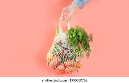 Mesh bag with vegetables and herbs in female hand. Woman hold string net shopping bag on pink background. Modern reusable shopping, eco friendly lifestyle, zero waste concept. Banner