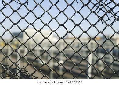 Mesh fencing, grunge, with blurred city in the background
