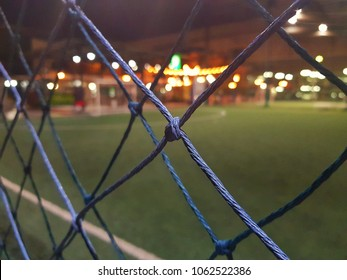 Mesh of lawn with light background of Futsal Stadium in the city.