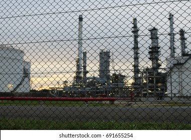 Mesh perimeter fence for oil refinery ensuring safety.