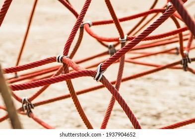 Mesh of red climbing ropes on playground.