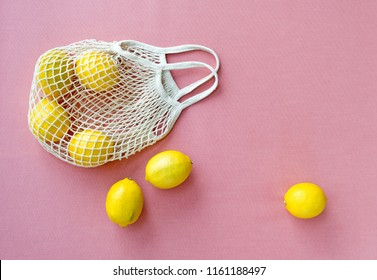 Mesh shopping bag with lemons on pink canvas background.