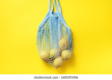 Mesh shopping bag with lemons on yellow paper background. Flat lay, top view. Zero waste, plastic free concept. Healthy clean eating diet and detox. Summer fruits.