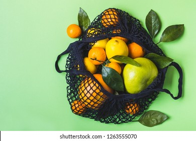 Mesh textile bag full of colorful fruit. Healthy food and zero waste concept.