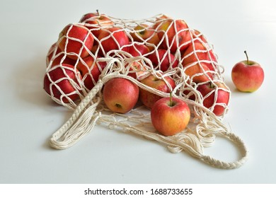 Mesh textile bag full of red apples. .Zero waste food shopping. Eco natural bags on white background. Eco friendly concept.Plastic free minimalist life style.Reuse, reduce, recycle. Say no to plastic