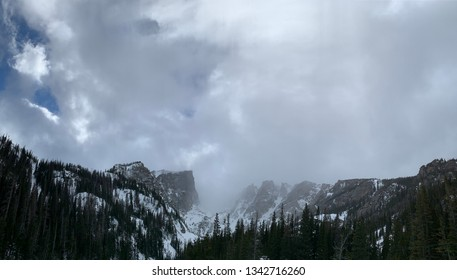 Mesmerizing and mystical panoramic shot of thick clouds rolling through Hallett Peak. This is a view from the emerald lake hiking trail at the Rocky Mountain National Park (located in Colorado, USA).