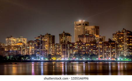 Mesmerizing photo of Colaba Skyline at night, as seen from Nariman Point of Marine Drive.  Buildings, Roadside and Night Market Light reflections may be seen in calm Arabian Sea, is like cherry on top