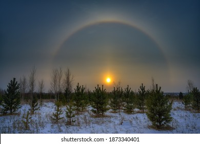 A mesmerizing sunset was observed on November 27, 2020 in the Urals (Russia). A multicolored arc from the sun is located on half of the sky. This rare phenomenon is a halo. Winter landscape with halo
