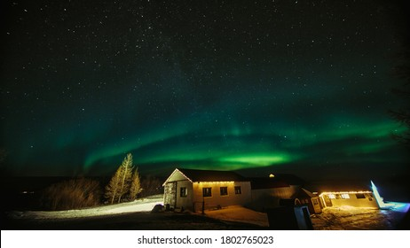 A mesmerizing view of aurora borealis on the star-filled night sky over trees and a house