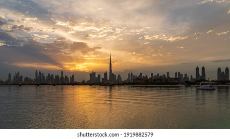 A mesmerizing view of Dubai's cityscape seen through sea waters with the reflection of a sunset
