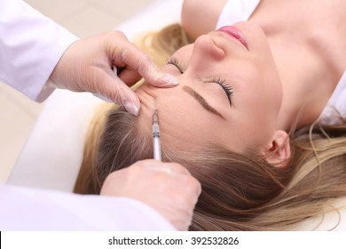 Mesotherapy. Beautiful woman gets an injection in her face.