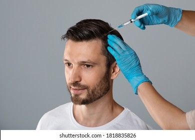 Mesotherapy for hair. Attractive man receiving injections in his head, grey studio background. Man having mesotherapy session at beauty salon, therapist in protective glove with syringe, copy space