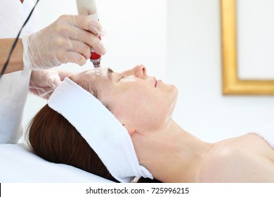 Mesotherapy microneedle, the woman at the beautician. Beautician performs a needle mesotherapy treatment on a woman's face