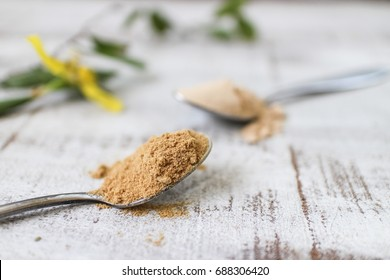 Mesquite and Lucuma Superfood Powder In Spoons. On wooden background.