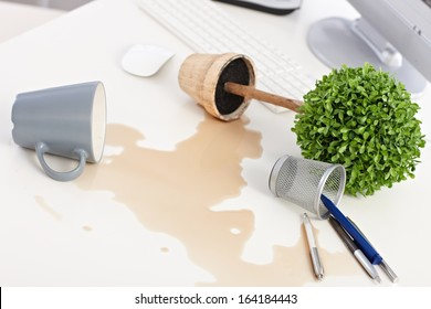Mess on desk, overturned plant and mug, spilled out coffee.