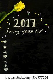 "The message ""2017 is my year to..."" was written with chalk on a blackboard. The message is frame with a yellow rose and candy stars."