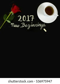 "The message ""2017, new beginnings"" was handwritten with chalk on blackboard. A rose and a cup of tea frame the message."