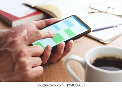 Message app on smartphone screen.Closeup of male hands touching smartphone screen at table.