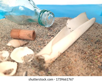 Message in a Bottle. Decorative background with a bottle on the sand with a sheet of paper for posting. Marine themes for decorating and creating collages and moods.