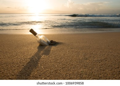 Message in a bottle half-buried in sand with ocean, sky and sunset in background