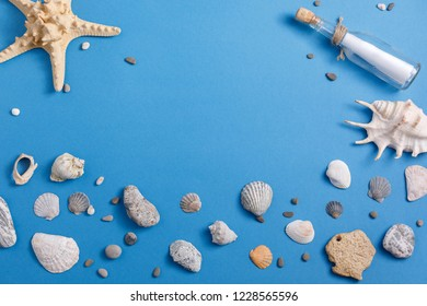 Message in a bottle on a turquoise background with seashells and starfish. View from above. Place under your text.