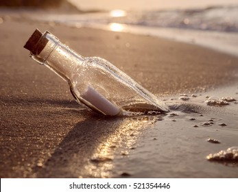 Message in the bottle washed ashore against the Sun setting down