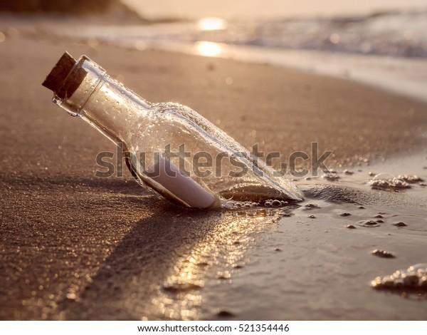 Flaschenpost an Land gewaschen gegen Sonnenuntergang