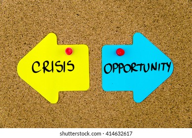 Message CRISIS versus OPPORTUNITY on yellow and blue paper notes as opposite arrows pinned on cork board with thumbtacks. Choice conceptual image