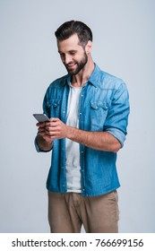 Message to friend. Handsome young man using phone with smile while standing against white background