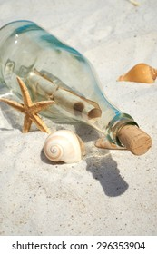 Message in a glass bottle lies on the sand beach with seashells and starfish