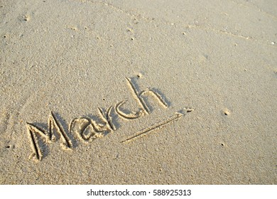 """Message hand writting """"March"""" on the sand at the beach."""