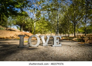 message of love with metal letters in a road in autumn season