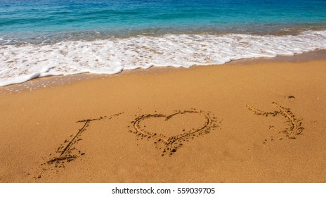 Message i love you on the sand with woman hand drawing on the beach
