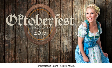 "message ""Oktoberfest - Sep 21. - Oct 06. 2019"" in German beautiful woman in a traditional bavarian dirndl in front of wooden background"