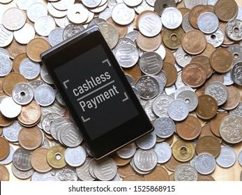 "the message on the screen is mobile phone said ""cashless payment"" with background of a lot of. Japanese coins as background.  the new electronic  payment concept in Japan."