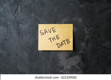 "message ""save the date"" on sticky note paper on cement wall texture background, loft style"