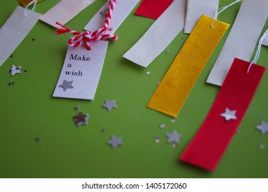 "a message tag ""Make a wish"" and strips of fancy paper"