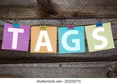 Message Tags written on a paper hanging on the clothesline on wooden background