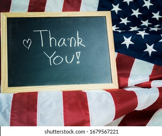 The message Thank you written in a chalkboard or blackboard with United States of America flag. Veteran military or independent day concept.