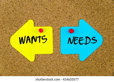 Message WANTS versus NEEDS on yellow and blue paper notes as opposite arrows pinned on cork board with thumbtacks. Choice conceptual image