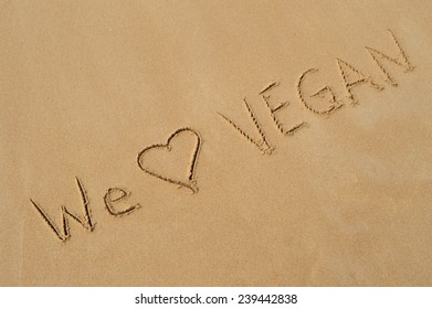 """The message """"we love vegan"""" written in the wet sand at the beach"""