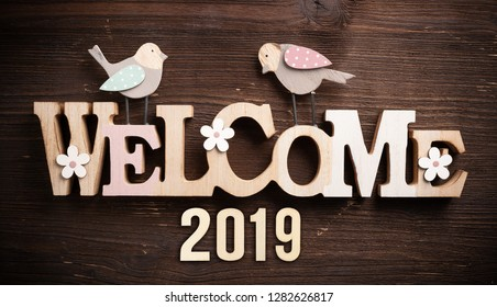 "message ""welcome 2019"" on rustic wooden background"