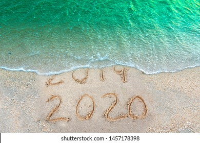 Message Year 2019 replaced by 2020 written on beach sand background. Good bye 2019 hello to 2020 happy New Year coming concept