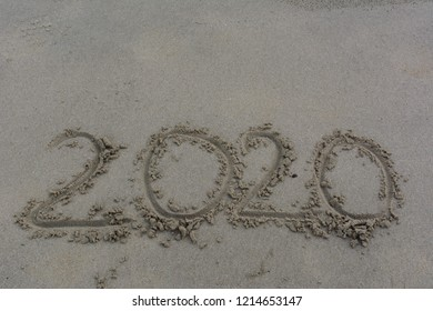 Message Year 2020 written on beach wet sand background. Can used for Happy new year 2020. Copy space on top for text or objects.