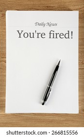 Message You're Fired on wooden table, top view