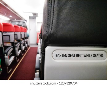 """The message""""FASTEN SEATBELT WHILE SEATED""""behind airplane seat for information to passenger in case of emergency for illustration aviation safety concept."""